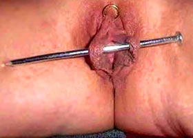 Driving a large nail into the labia and clitoris
